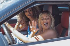 Coquettish girls in car flirting with pedestrian. Trendy and confident diverse women sitting inside of car and flirting with people outside having fun and royalty free stock photos