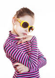 Coquettish little girl wearing striped blouse and yellow sunglasses Royalty Free Stock Images