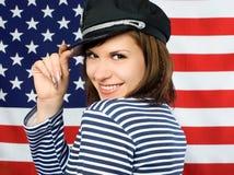 Coquettish sailor standing near the American flag Stock Photo