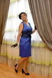 The coquettish woman of average years in a blue dress is by the window Stock Photos