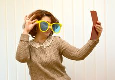 The coquettish woman in big sunglasses smiles, looking at herself in a mirror Stock Photos