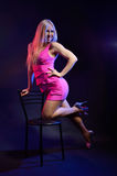 Coquettish woman leaning on the chair. Flirtatious woman leans on the chair in the dark background. She is looking at the camera. Blonde girl is wearing a pink stock image