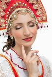 Coquettish young woman portrait in russian traditional costume. Red sarafan and kokoshnik Studio shot isolated on white stock photo
