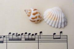 Coquillages et papier avec les notes musicales Photos stock