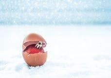 coquille d'oeufs avec la boule de Noël sur le conce de fond de Noël de neige Photographie stock