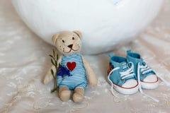 Coquille de panier des oeufs de pâques, du bébé garçon plat de chaussures et d'un ours de nounours avec un plan rapproché de coeu Photos stock