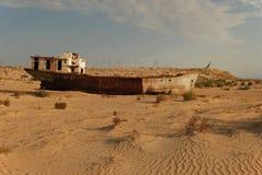 Coquille rouillée de bateau se situant dans le désert Image stock