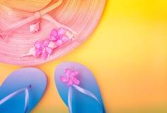 Coquilles bleues de mer de pantoufles de fleurs tropicales de rose du chapeau de paille des femmes sur le fond jaune couleur pêch images stock