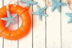 Coquilles décoratives de mer de bouée de sauvetage, d'ancre et d'étoiles de mer au-dessus de fond blanc en bois Image stock
