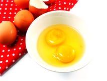 Coquilles d'oeuf cassées avec des jaunes d'oeuf dans la cuvette en céramique sur la nappe rouge de point de polka Images stock