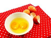 Coquilles d'oeuf cassées avec des jaunes d'oeuf dans la cuvette en céramique sur la nappe rouge de point de polka Image libre de droits