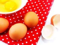 Coquilles d'oeuf cassées avec des jaunes d'oeuf dans la cuvette en céramique avec le tissu rouge de point de polka Photo libre de droits
