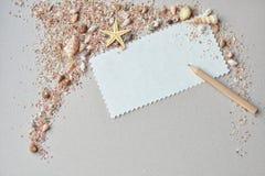 Coquilles de mer, sable rose et carte d'invitation avec un crayon sur un fond de papier Photographie stock libre de droits