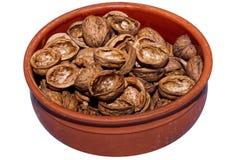 Coquilles de noix dans une cuvette d'argile photos stock