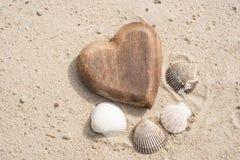 Coquilles en bois d'und de coeur sur le sable sur la plage Photo stock