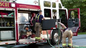 Coquitlam firefighters wrap up their water hoses on fire truck stock video footage