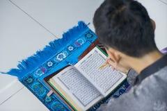 Corán musulmán masculino de la lectura en casa Imágenes de archivo libres de regalías