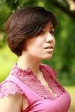 Coréen émotif regardant pensivement dans l'appareil-photo, dres roses Image stock