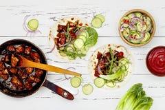 Coréen ralentissez le tacos cuit de boeuf avec le slaw de concombre et le ketchup asiatiques de sriracha Vue supérieure, configur images stock