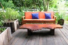 Cor alaranjada do sofá e tabela de madeira no jardim imagem de stock royalty free