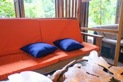 Cor alaranjada do sofá e tabela de madeira no jardim imagens de stock