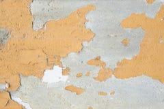A cor alaranjada pintada na parede do cimento está descascando foto de stock
