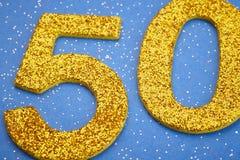 Cor amarela do número cinqüênta sobre um fundo azul anniversary Imagens de Stock Royalty Free