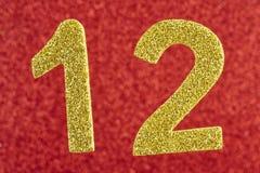 Cor amarela do número doze sobre um fundo vermelho anniversary Fotos de Stock
