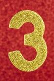 Cor amarela do número três sobre um fundo vermelho anniversary Fotografia de Stock