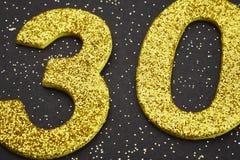 Cor amarela do número trinta sobre um fundo preto anniversary Imagem de Stock Royalty Free
