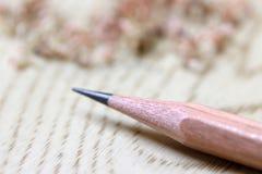 A cor de madeira do lápis afiado e focaliza para fora lápis da moeda de um centavo no assoalho de madeira fotos de stock royalty free