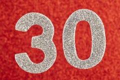 Cor de prata do número trinta sobre um fundo vermelho anniversary H Foto de Stock Royalty Free