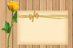 Cor-de-rosa bonito amarelo e cartão com curva dourada na textura de madeira Fotografia de Stock