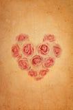 A cor-de-rosa da forma do coração levantou-se no papel marrom velho do grunge Fotografia de Stock