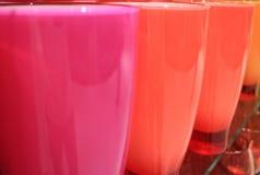 Cor-de-rosa vívido e a laranja coloriram vidros alinhados na prateleira Imagem de Stock
