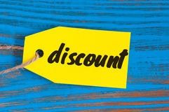 Cor do amarelo da etiqueta da etiqueta do disconto no fundo de madeira azul Fotografia de Stock Royalty Free