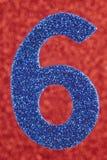 Cor do azul do número seis sobre um fundo vermelho anniversary Fotos de Stock Royalty Free