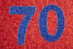 Cor do azul do número setenta sobre um fundo vermelho anniversary Foto de Stock