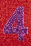 Cor do roxo do número quatro sobre um fundo vermelho anniversary Fotos de Stock Royalty Free