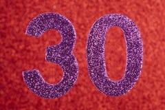 Cor do roxo do número trinta sobre um fundo vermelho anniversary Fotografia de Stock