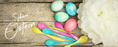 A cor pastel coloriu ovos da páscoa, colheres e a flor de papel, texto alemão Imagens de Stock