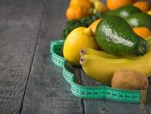 Cor verde de medição da fita com fruto tropical em uma tabela de madeira Imagens de Stock