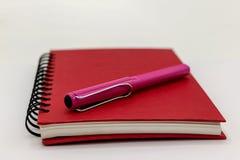 Cor vermelha do caderno e pena cor-de-rosa Imagens de Stock Royalty Free