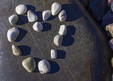 Coração bonito feito das pedras sobre a rocha Pedras arranjadas na forma do coração Fotografia de Stock Royalty Free