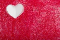 Coração branco em um fundo do sisal vermelho Foto de Stock Royalty Free