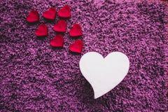 Coração branco grande com os corações cor-de-rosa menores que vão acima Fundo roxo foto de stock royalty free