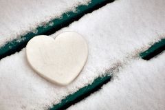 Coração branco no banco coberto de neve Rosa vermelha fotografia de stock