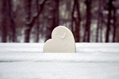 Coração branco no banco de parque coberto de neve Símbolo do amor puro fotografia de stock