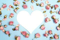 Coração-cartão vazio com as rosas cor-de-rosa pequenas no fundo azul lugar Imagens de Stock