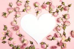 Coração-cartão vazio com as rosas secas pequenas no fundo cor-de-rosa lugar Fotos de Stock
